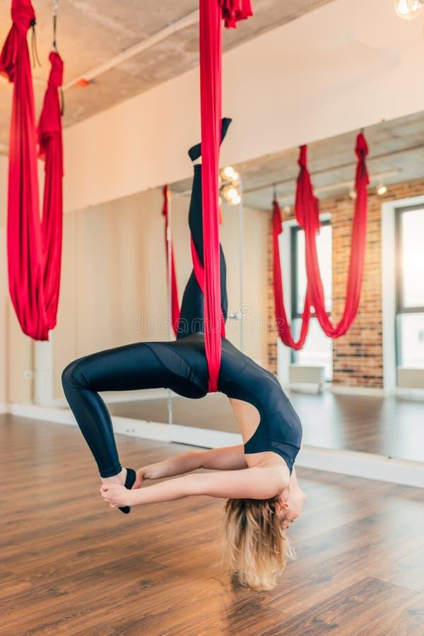 Giovane donna in tuta nera che si esercita antigravità di yoga nella classe immagine stock libera da diritti