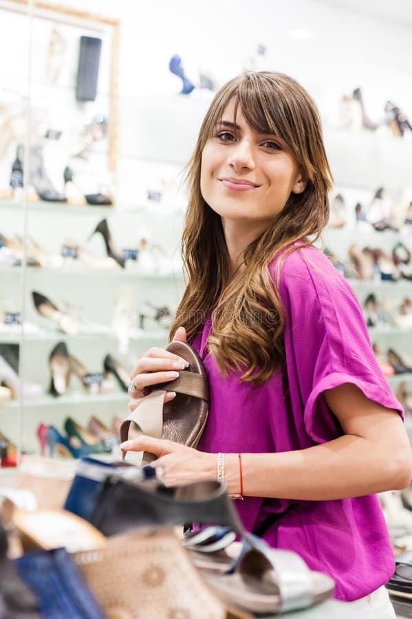 Giovane donna in un negozio di scarpe immagini stock