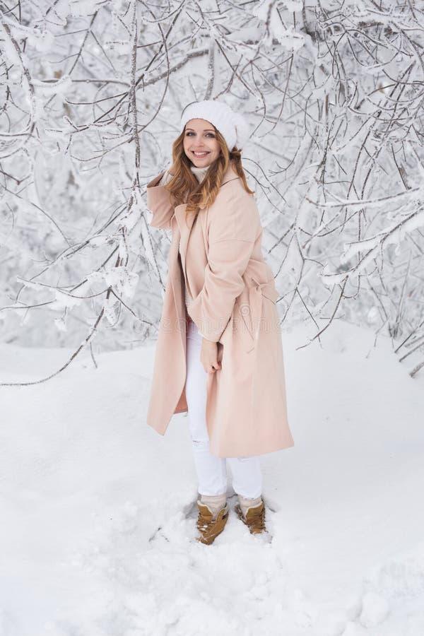 Giovane donna in un rivestimento beige nel parco di inverno fotografia stock