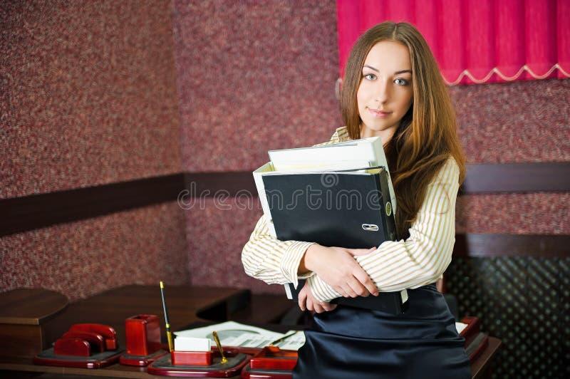 Giovane donna in un ufficio con dispositivi di piegatura fotografia stock libera da diritti