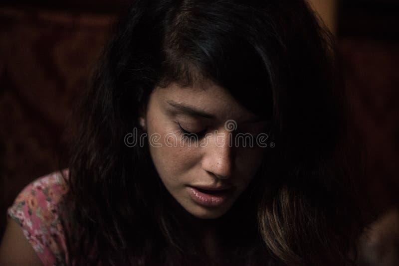 Giovane donna in un umore triste che si siede su uno strato con una luce naturale della finestra nel suo fronte immagine stock libera da diritti