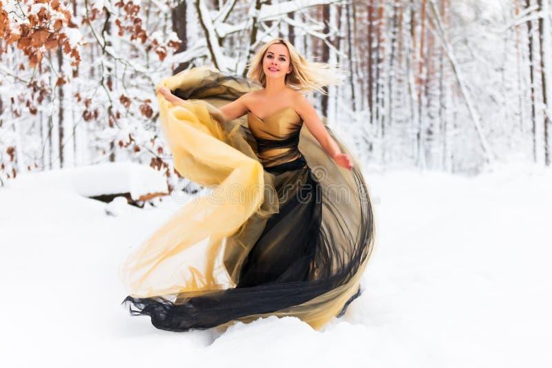Giovane donna in un vestito lungo nella foresta di inverno fotografia stock libera da diritti