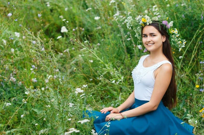 Giovane donna in una corona dai wildflowers e dall'erba fotografie stock libere da diritti
