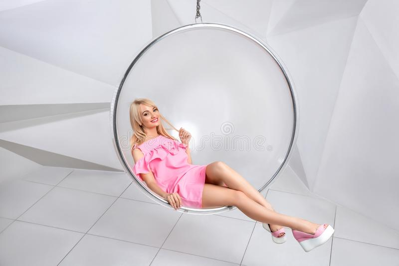 Giovane donna in una sedia su un fondo bianco geometry Bionda in un vestito rosa in una sedia rotonda di plastica immagini stock