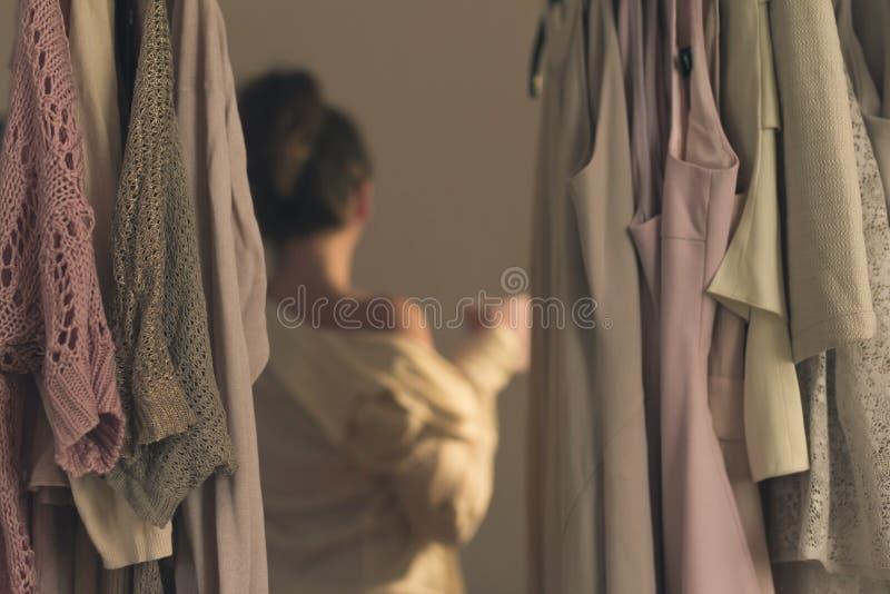 Giovane donna Unfocused con la tazza di caffè e condizione davanti al suo primo mattino del guardaroba fotografia stock libera da diritti