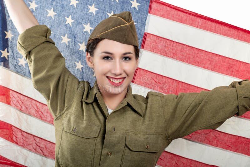 Giovane donna in uniforme militare degli Stati Uniti che sostiene una bandiera americana fotografia stock