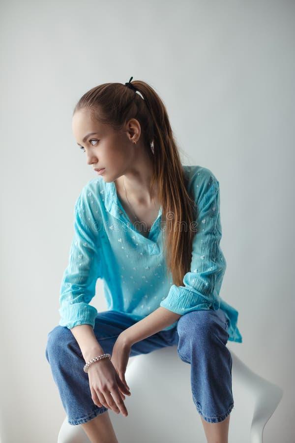 Giovane donna urbana alla moda sicura che distoglie lo sguardo mentre sedendosi sulla sedia, su fondo grigio fotografia stock