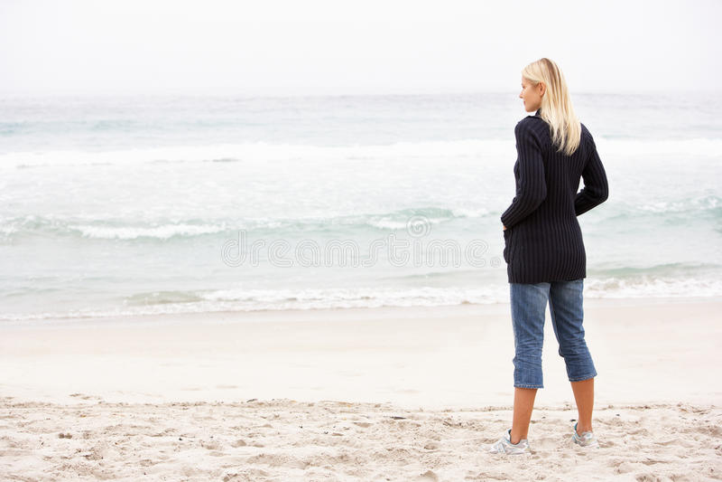 Giovane donna in vacanza che si leva in piedi sulla spiaggia di inverno immagini stock