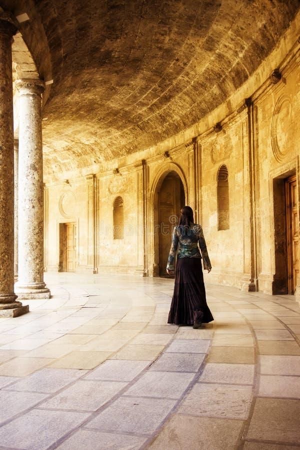 Giovane donna in vecchi corridoi immagini stock