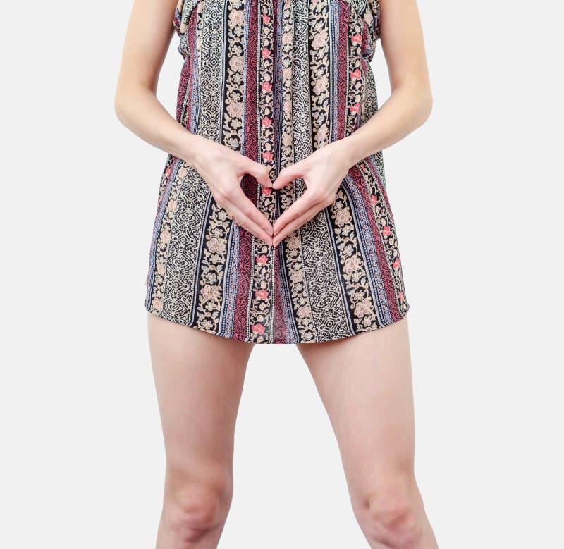 Giovane donna vestita con le mani in forma di cuore a livello di pancia Amore, concepimento, pianificazione della gravidanza fotografia stock libera da diritti