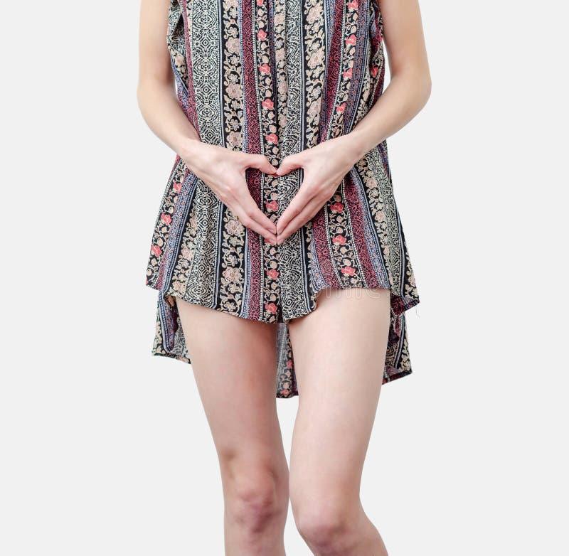Giovane donna vestita con le mani in forma di cuore a livello di pancia Amore, concepimento, pianificazione della gravidanza fotografia stock