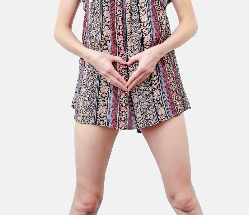 Giovane donna vestita con le mani in forma di cuore a livello di pancia Amore, concepimento, pianificazione della gravidanza fotografie stock libere da diritti