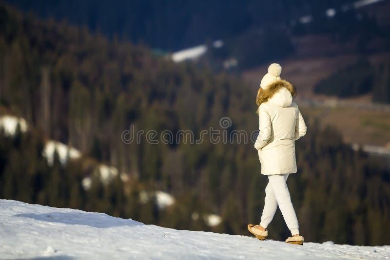 Giovane donna in vestiti bianchi di inverno che cammina all'aperto immagine stock libera da diritti