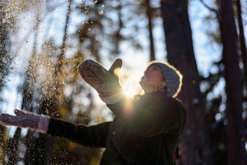 Giovane donna in vestiti di inverno che giocano con la neve nel legno La gioia dell'inverno, la ragazza getta nell'aria la neve f fotografie stock libere da diritti