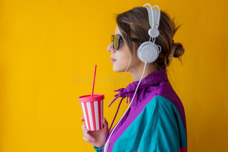 Giovane donna in vestiti di stile 90s con la tazza e le cuffie fotografie stock