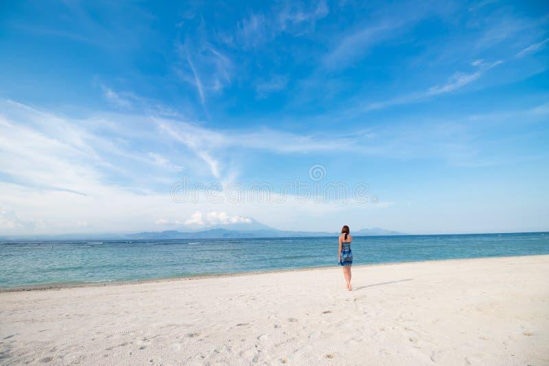 Giovane donna in vestito blu che cammina sulla spiaggia dell'isola tropicale Nusa Lembongan, Indonesia Cielo stupefacente, vista  fotografia stock libera da diritti