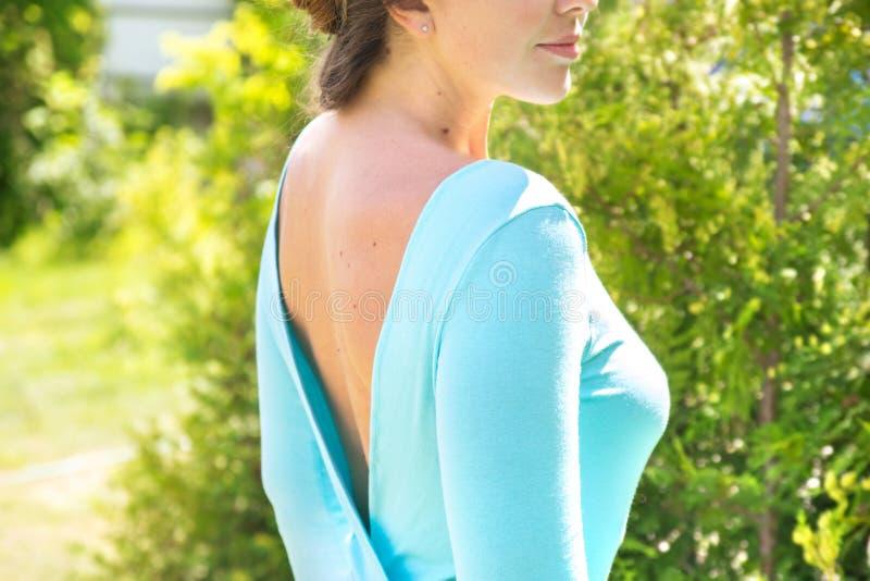 Giovane donna in vestito blu con il ritratto posteriore nudo nei clo di estate immagini stock libere da diritti