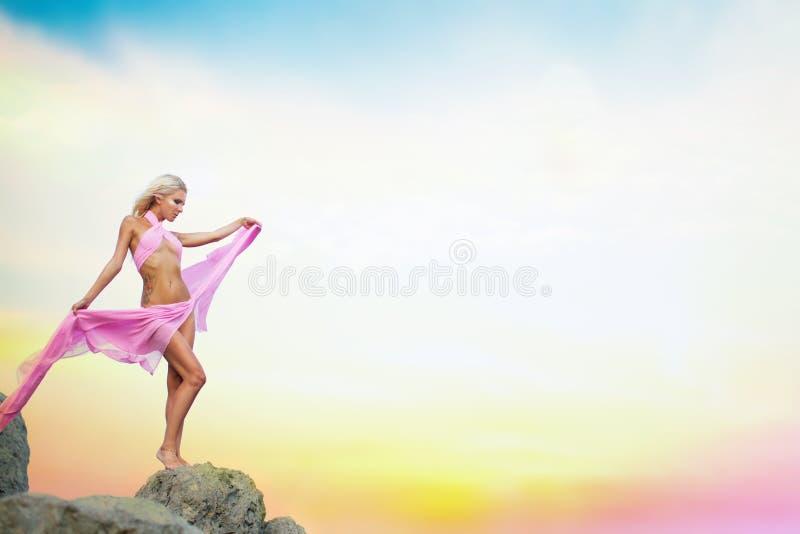 Giovane donna in vestito che sta su una roccia fotografia stock libera da diritti
