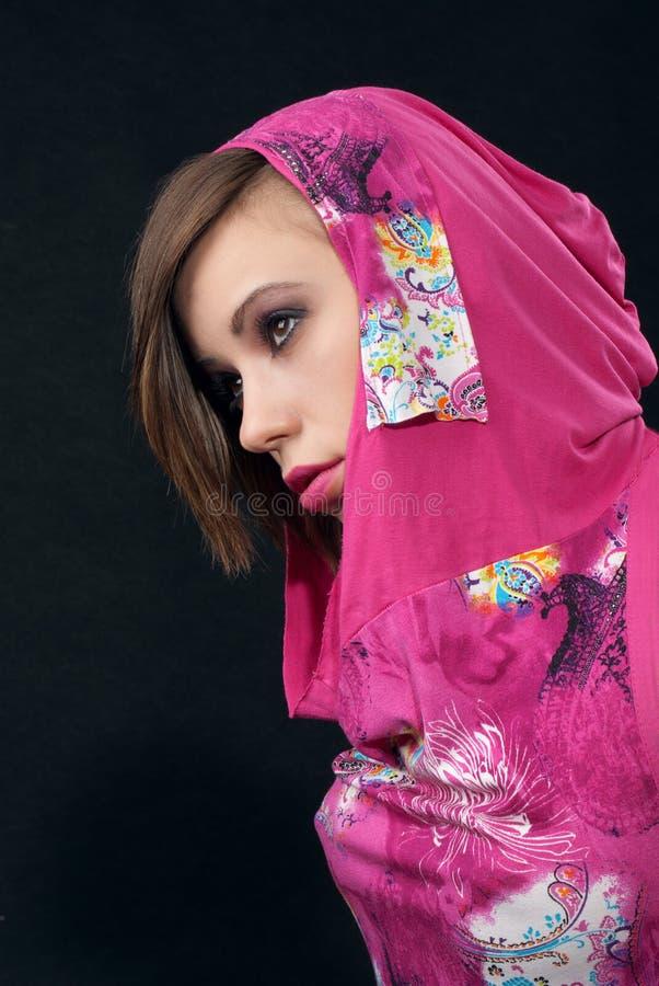 Giovane donna in vestito cremisi su priorità bassa nera fotografia stock libera da diritti