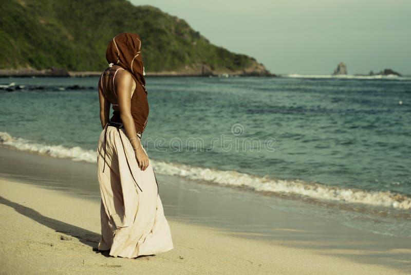 Giovane donna in vestito da estate che fa una pausa mare blu immagini stock libere da diritti
