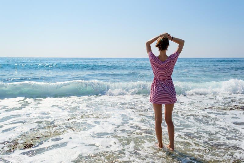Giovane donna in vestito da estate che fa una pausa mare blu e che guarda all'orizzonte fotografie stock libere da diritti