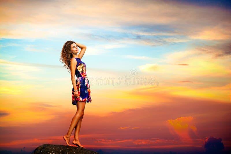Giovane donna in vestito da estate che sta su una roccia fotografia stock libera da diritti