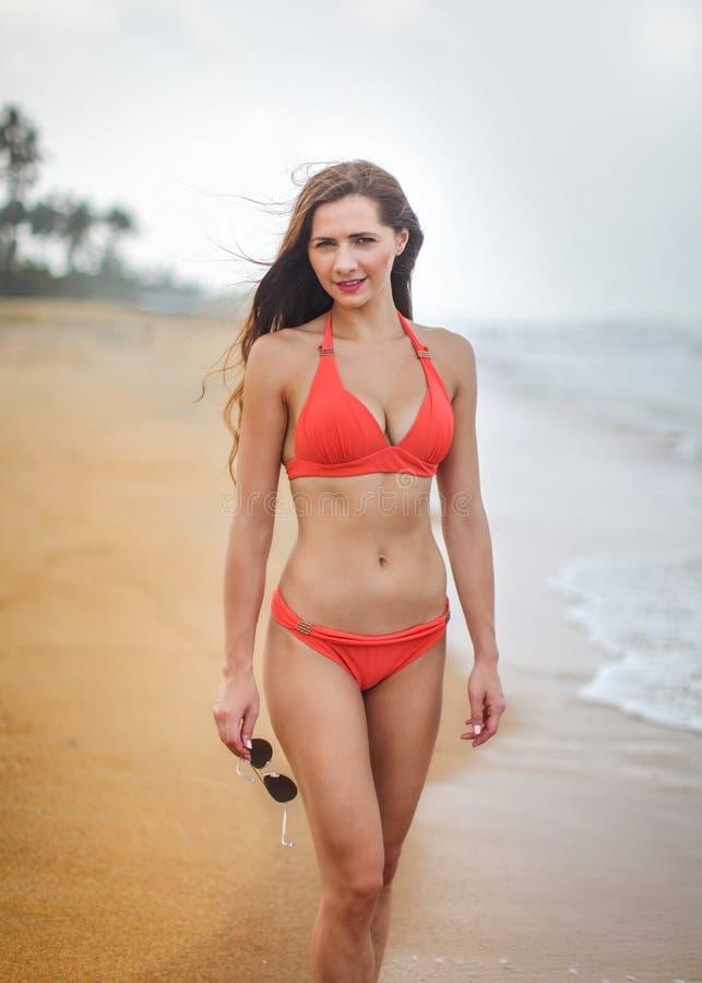 Giovane donna in vestito di nuotata rosso del bikini con l'ente sportivo, tenente l'Unione Sovietica fotografia stock libera da diritti