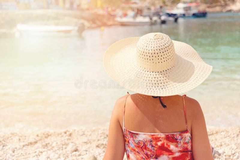 Giovane donna in vestito e cappello da estate che stanno sulla sabbia e che guardano all'il porto di Oporto Vromi, Grecia immagini stock libere da diritti