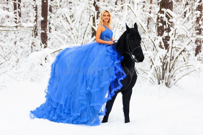 Giovane donna in vestito lungo che monta un cavallo nell'inverno fotografia stock