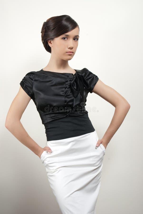 Giovane donna in vestito nero-bianco in stydio immagine stock libera da diritti