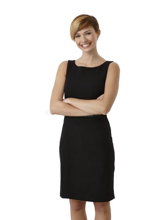 Giovane donna in vestito nero con le armi attraversate immagini stock
