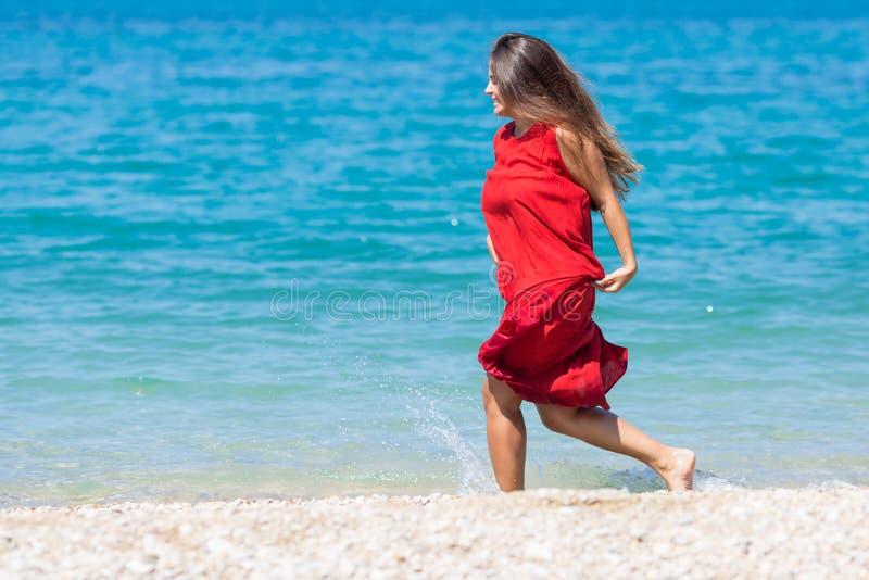 Giovane donna in vestito rosso lungo che corre lungo la spiaggia immagini stock libere da diritti