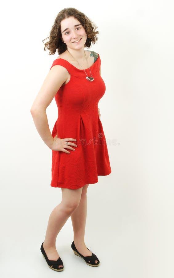 Giovane donna in vestito rosso su fondo grigio bianco in integrale fotografia stock