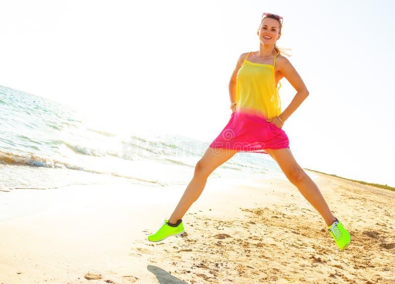 Giovane donna in vestito variopinto sulla spiaggia nel salto di sera immagine stock