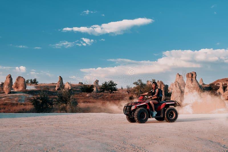 Giovane donna in viaggio safari nel deserto guidando Quad ATV fotografia stock libera da diritti