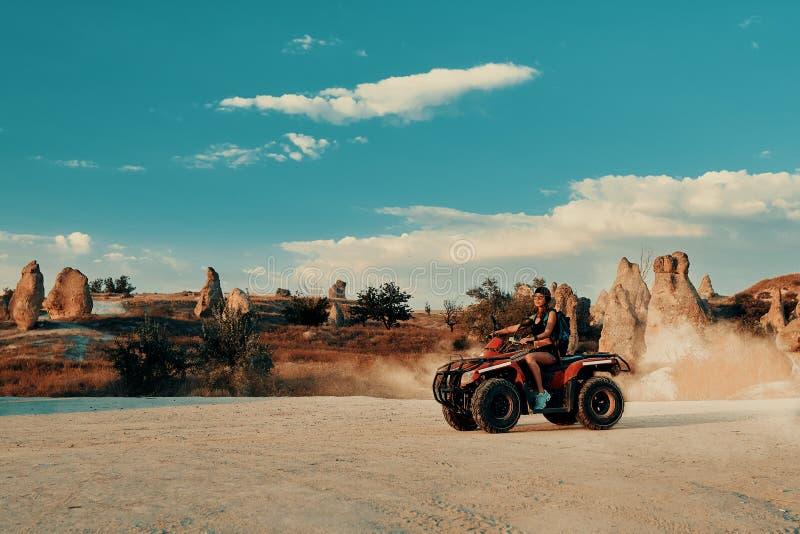 Giovane donna in viaggio safari nel deserto guidando Quad ATV fotografia stock
