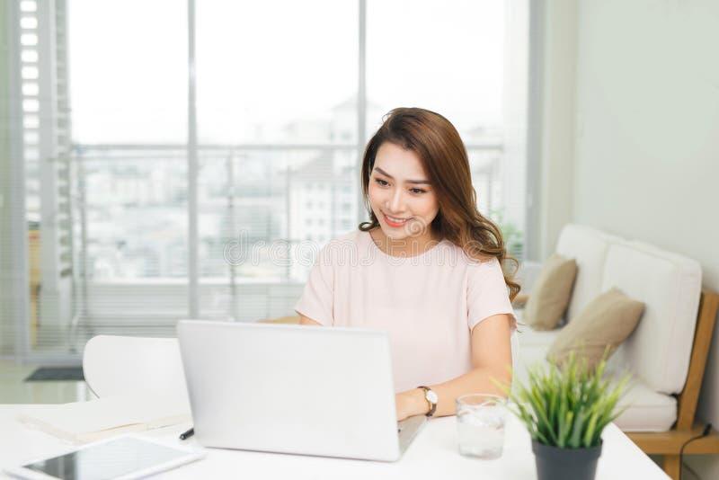 Giovane donna vietnamita graziosa che lavora con il computer portatile in ufficio immagini stock libere da diritti