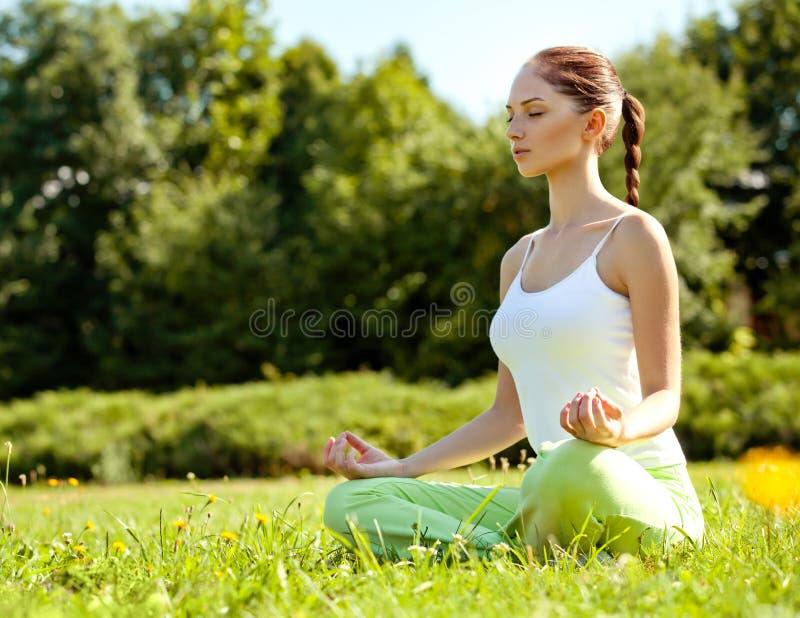Giovane e bella donna che fa gli esercizi di yoga. Fondo di yoga immagini stock libere da diritti