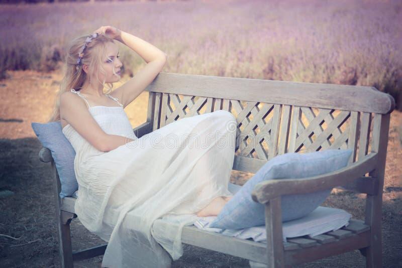 Giovane e bella donna che si siede su un banco fotografia stock libera da diritti
