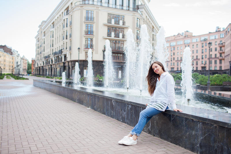 Giovane e bella ragazza che si siede alla fontana e che sorride in un nuovo complesso residenziale fotografia stock libera da diritti