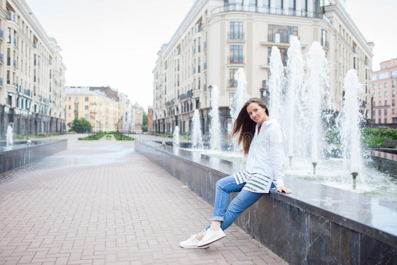 Giovane e bella ragazza che si siede alla fontana e che sorride in un nuovo complesso residenziale fotografie stock