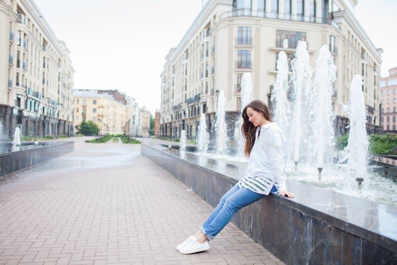 Giovane e bella ragazza che si siede alla fontana e che sorride in un nuovo complesso residenziale immagini stock