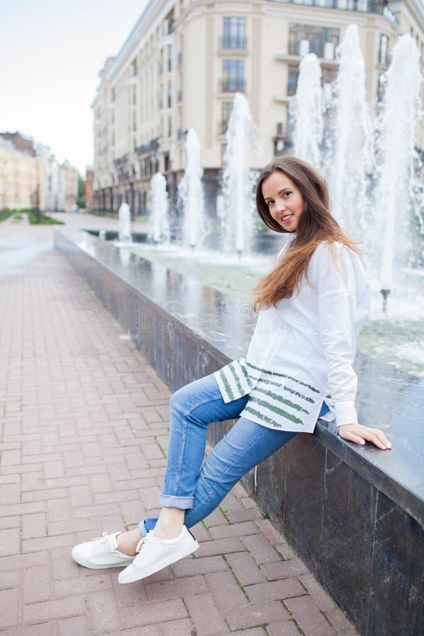 Giovane e bella ragazza che si siede alla fontana e che sorride in un nuovo complesso residenziale immagine stock libera da diritti