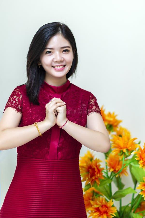 Giovane e bella ragazza cinese che desidera gong Xi Fa Chai a casa fotografia stock libera da diritti