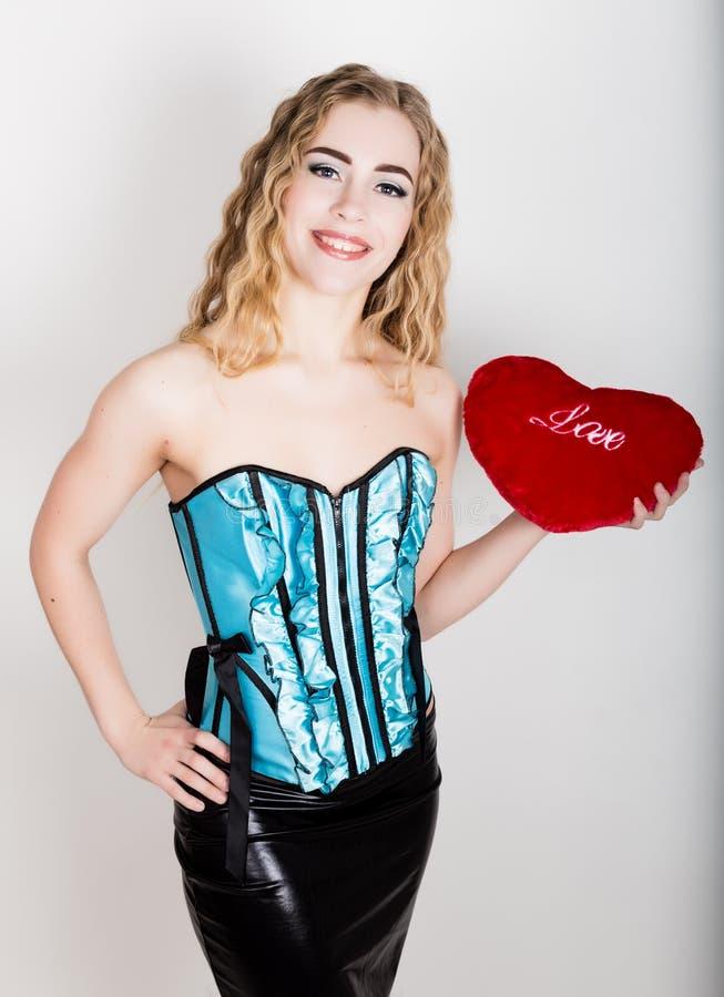 Giovane e bella ragazza riccia in corsetto blu che tiene un cuscino rosso del cuore fotografia stock