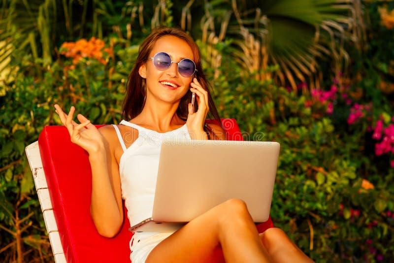 Giovane e bellissima donna viaggiatrice freelancer seduta su un lunotto con un laptop che parla al telefono sulla costa fotografia stock