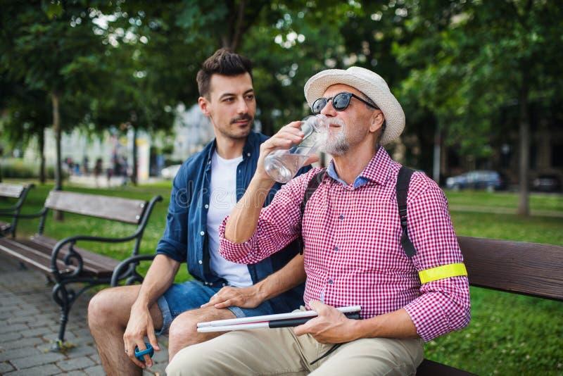 Giovane e cieco con un bastone bianco seduto sulla panchina nel parco della città immagini stock