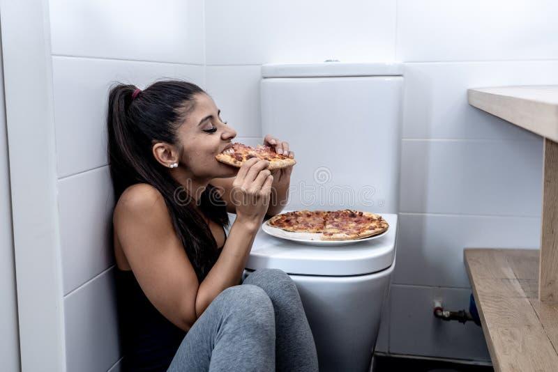 Giovane e giovane donna affetta da bulimia triste attraente che ritiene cibo colpevole e malato mentre sedendosi sul pavimento ac fotografia stock libera da diritti