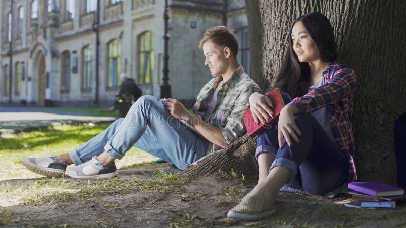 Giovane e donna che si siedono sotto l'albero, essendo timido alla prima riunione, mancanza di abilità fotografia stock libera da diritti