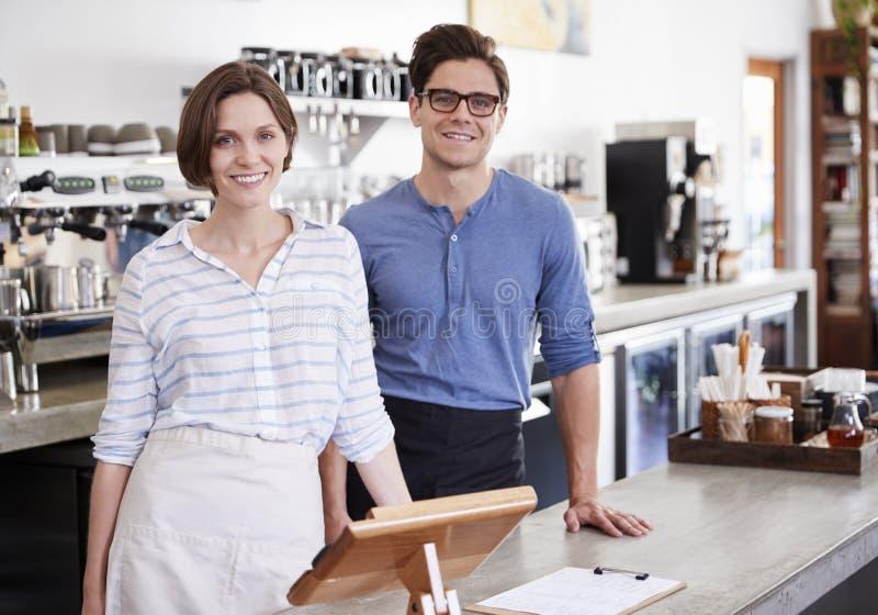 Giovane e donna felici dietro il contatore alla caffetteria immagine stock